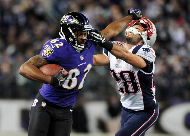 Dec 22, 2013; Baltimore, MD, USA; Baltimore Ravens wide receiver Torrey Smith (82) gives a stiff arm to New England Patriots safety Steve Gregory (28) at M&T Bank Stadium. Mandatory Credit: Evan Habeeb-USA TODAY Sports