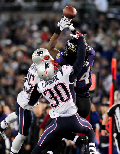 Dec 22, 2013; Baltimore, MD, USA; Baltimore Ravens wide receiver Marlon Brown (14) has the ball knocked away by New England Patriots defensive back Duron Harmon (30) and cornerback Kyle Arrington (25) at M&T Bank Stadium. Mandatory Credit: Evan Habeeb-USA TODAY Sports