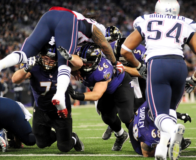 Dec 22, 2013; Baltimore, MD, USA; Baltimore Ravens offensive guard Marshall Yanda (73) and center Gino Gradkowski (66) block for quarterback Joe Flacco (5) on a 1 yard touchdown run in the fourth quarter against the New England Patriots at M&T Bank Stadium. Mandatory Credit: Evan Habeeb-USA TODAY Sports