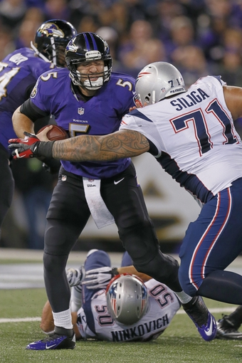 Dec 22, 2013; Baltimore, MD, USA; Baltimore Ravens quarterback Joe Flacco (5) sacked by New England Patriots tackle Seaver Siliga (71) at M&T Bank Stadium. Mandatory Credit: Mitch Stringer-USA TODAY Sports