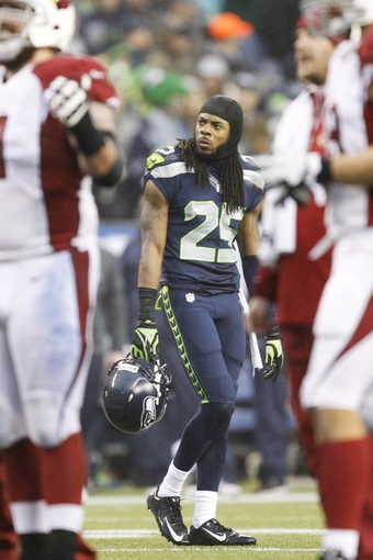 Dec 22, 2013; Seattle, WA, USA; Seattle Seahawks cornerback Richard Sherman (25) watches a replay during an official challenge by the Seattle Seahawks against the Arizona Cardinals during the fourth quarter at CenturyLink Field. Mandatory Credit: Joe Nicholson-USA TODAY Sports