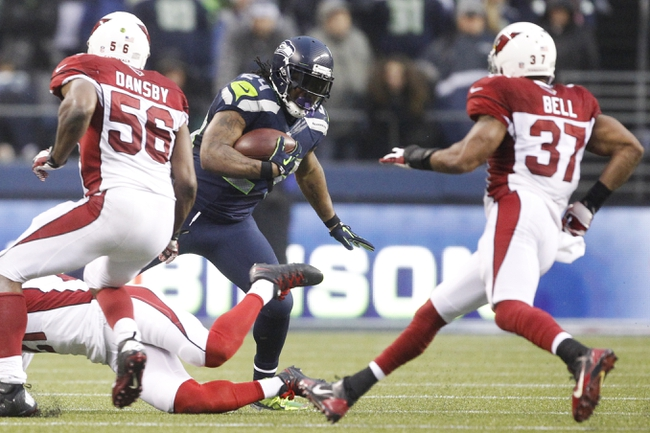 Dec 22, 2013; Seattle, WA, USA; Seattle Seahawks running back Marshawn Lynch (24) rushes against the Arizona Cardinals during the fourth quarter at CenturyLink Field. Mandatory Credit: Joe Nicholson-USA TODAY Sports