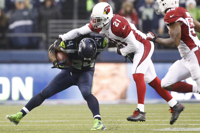 Dec 22, 2013; Seattle, WA, USA; Arizona Cardinals cornerback Patrick Peterson (21) tackles Seattle Seahawks running back Marshawn Lynch (24) during the fourth quarter at CenturyLink Field. Mandatory Credit: Joe Nicholson-USA TODAY Sports
