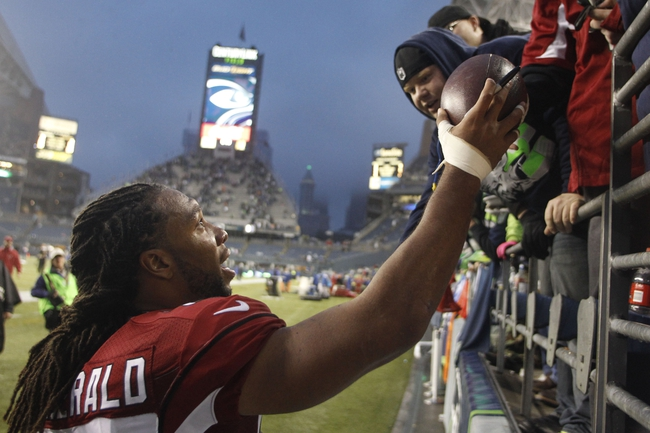 Dec 22, 2013; Seattle, WA, USA; Arizona Cardinals wide receiver Larry Fitzgerald (11) hands an autographed football to a fan following a 17-10 Arizona victory against the Seattle Seahawks at CenturyLink Field. Mandatory Credit: Joe Nicholson-USA TODAY Sports