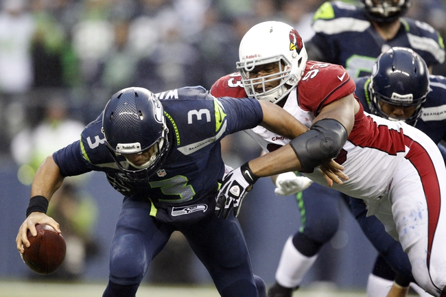 Dec 22, 2013; Seattle, WA, USA; Arizona Cardinals defensive end Calais Campbell (93) sacks Seattle Seahawks quarterback Russell Wilson (3) during the fourth quarter at CenturyLink Field. Mandatory Credit: Joe Nicholson-USA TODAY Sports