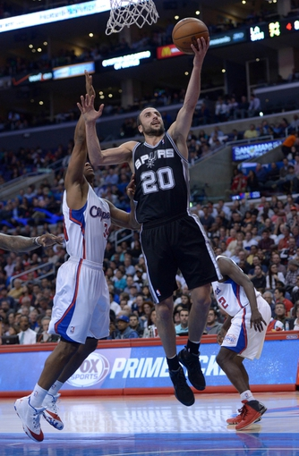 Dec 16, 2013; Los Angeles, CA, USA; San Antonio Spurs guard Manu Ginobili (20) shoots the ball as Los Angeles Clippers forward Willie Green (34) defends at Staples Center. The Clippers defeated the Spurs 115-92. Mandatory Credit: Kirby Lee-USA TODAY Sports