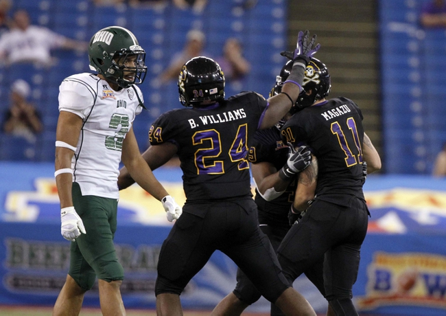 Dec 23, 2013; St. Petersburg, FL, USA; East Carolina Pirates defensive back Damon Magazu (11) is congratulated by teammates after he intercepted the ball against the Ohio Bobcats  during the second half at the 2013 Beef O Bradys Bowl at Tropicana Field. East Carolina won 37-20. Mandatory Credit: Kim Klement-USA TODAY Sports