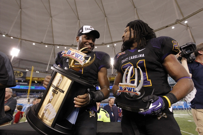 Dec 23, 2013; St. Petersburg, FL, USA; East Carolina Pirates wide receiver Cedric Thompson (8) and running back Vintavious Cooper (21) hold the trophy after they beat the Ohio Bobcats at the 2013 Beef O Bradys Bowl at Tropicana Field. East Carolina won 37-20. Mandatory Credit: Kim Klement-USA TODAY Sports