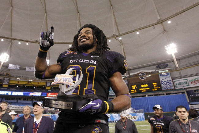 Dec 23, 2013; St. Petersburg, FL, USA; East Carolina Pirates running back Vintavious Cooper (21) reacts after he was named MVP of the game against the Ohio Bobcats at the 2013 Beef O Bradys Bowl at Tropicana Field. Eastern Carolina Pirates defeated the Ohio Bobcats 37-20. Mandatory Credit: Kim Klement-USA TODAY Sports