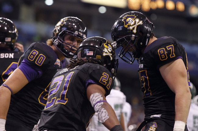 Dec 23, 2013; St. Petersburg, FL, USA; East Carolina Pirates running back Vintavious Cooper (21) is congratulated by running back Zico Pasut (87) and wide receiver Bryce Williams (80) after they scored a touchdown against the Ohio Bobcats during the second half at the 2013 Beef O Bradys Bowl at Tropicana Field. Eastern Carolina Pirates defeated the Ohio Bobcats 37-20. Mandatory Credit: Kim Klement-USA TODAY Sports