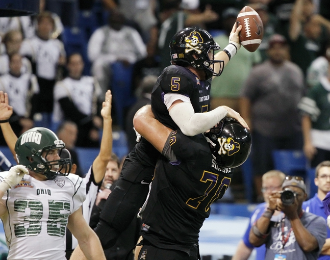 Dec 23, 2013; St. Petersburg, FL, USA; East Carolina Pirates quarterback Shane Carden (5) reacts with offensive linesman Will Simmons (70) after scoring a touchdown against the Ohio Bobcats in the second half at the 2013 Beef O Bradys Bowl at Tropicana Field. Eastern Carolina Pirates defeated the Ohio Bobcats 37-20. Mandatory Credit: Kim Klement-USA TODAY Sports