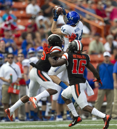 Dec 24, 2013; Honolulu, HI, USA; Boise State Broncos wide receiver Kirby Moore (34) pulls in a pass over Oregon State Beavers safety Ryan Murphy (25) and cornerback Rashaad Reynolds (16) during the 2nd quarter of the 2013 Hawaii Bowl at Aloha Stadium. Mandatory Credit: Marco Garcia-USA TODAY Sports