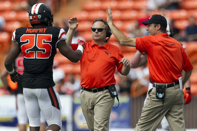 Dec 24, 2013; Honolulu, HI, USA; Oregon State Beavers safety Ryan Murphy (25) gets a high five from defensive coordinator Mike Banker (middle) and head coach Mike Riley during the 2nd quarter of the 2013 Hawaii Bowl against the Boise State Broncos at Aloha Stadium. Mandatory Credit: Marco Garcia-USA TODAY Sports