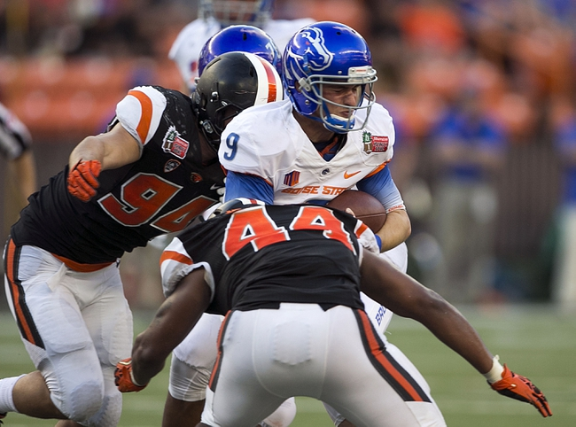 Dec 24, 2013; Honolulu, HI, USA; Boise State Broncos quarterback Grant Hedrick (9) gets sacked by Oregon State Beavers linebacker Jabral Johnson (44) and defensive end Devon Kell (94) in the third quarter at the 2013 Hawaii Bowl at Aloha Stadium. Mandatory Credit: Marco Garcia-USA TODAY Sports