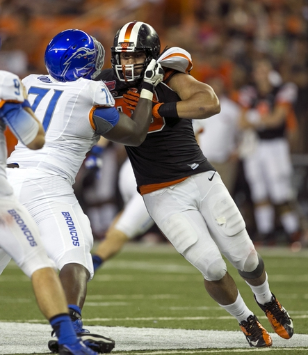 Dec 24, 2013; Honolulu, HI, USA; Oregon State Beavers defensive end Scott Crichton (95) is held back by Boise State Broncos offensive linesman Rees Odhiambo (71) during the fourth quarter at the 2013 Hawaii Bowl at Aloha Stadium. Mandatory Credit: Marco Garcia-USA TODAY Sports