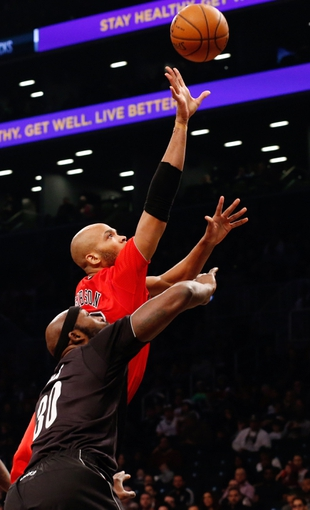 Dec 25, 2013; Brooklyn, NY, USA;  Chicago Bulls power forward Taj Gibson (22) shoots over Brooklyn Nets power forward Reggie Evans (30) during the first quarter at Barclays Center. Mandatory Credit: Anthony Gruppuso-USA TODAY Sports