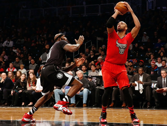 Dec 25, 2013; Brooklyn, NY, USA; Chicago Bulls power forward Taj Gibson (22) shoots over Brooklyn Nets power forward Reggie Evans (30) during the second quarter at Barclays Center. Mandatory Credit: Anthony Gruppuso-USA TODAY Sports
