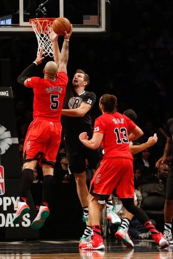 Dec 25, 2013; Brooklyn, NY, USA; Brooklyn Nets power forward Mirza Teletovic (33) fouls Chicago Bulls power forward Carlos Boozer (5) during the third quarter  at Barclays Center. Chicago Bulls won 95-78.  Mandatory Credit: Anthony Gruppuso-USA TODAY Sports