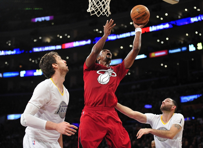 December 25, 2013; Los Angeles, CA, USA; Miami Heat center Chris Bosh (1) moves to the basket against the defense of Los Angeles Lakers center Pau Gasol (16) and point guard Jordan Farmar (1) during the first half at Staples Center. Mandatory Credit: Gary A. Vasquez-USA TODAY Sports