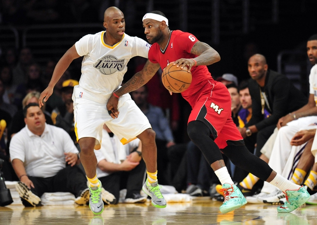 December 25, 2013; Los Angeles, CA, USA; Miami Heat small forward LeBron James (6) moves the ball against the defense of Los Angeles Lakers shooting guard Jodie Meeks (20) during the second half at Staples Center. Mandatory Credit: Gary A. Vasquez-USA TODAY Sports