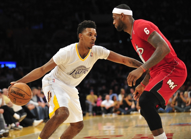 December 25, 2013; Los Angeles, CA, USA; Los Angeles Lakers small forward Nick Young (0) moves the ball against the defense of Miami Heat small forward LeBron James (6) during the second half at Staples Center. Mandatory Credit: Gary A. Vasquez-USA TODAY Sports