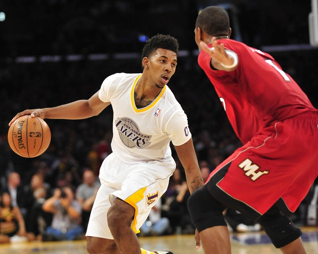 December 25, 2013; Los Angeles, CA, USA; Los Angeles Lakers small forward Nick Young (0) moves the ball against the defense of Miami Heat center Chris Bosh (1) during the second half at Staples Center. Mandatory Credit: Gary A. Vasquez-USA TODAY Sports