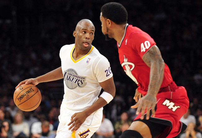 December 25, 2013; Los Angeles, CA, USA; Los Angeles Lakers shooting guard Jodie Meeks (20) moves the ball against the defense of Miami Heat  power forward Udonis Haslem (40) during the second half at Staples Center. Mandatory Credit: Gary A. Vasquez-USA TODAY Sports