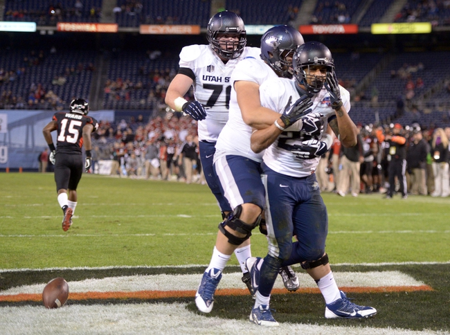 Dec 26, 2013; San Diego, CA, USA; Utah State Aggies running back Joey DeMartino (28) celebrates with teammates Rick Ali'ifua (95) and Jake Simonich (76) after scoring on a 1-yard touchdown run in the fourth quarter against the Northern Illinois Huskies during the 2013 Poinsettia Bowl at Qualcomm Stadium. Mandatory Credit: Kirby Lee-USA TODAY Sports
