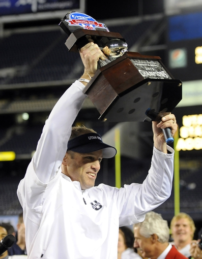 Dec 26, 2013; San Diego, CA, USA; Utah State Aggies head coach Matt Wells celebrates with the Poinsettia Bowl trophy following a win against the Northern Illinois Huskies at Qualcomm Stadium. The Aggies won 21-14. Mandatory Credit: Christopher Hanewinckel-USA TODAY Sports