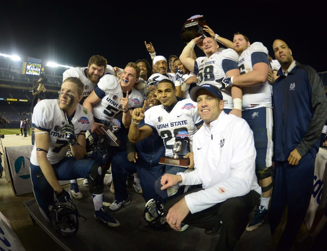 Dec 26, 2013; San Diego, CA, USA; Utah State running back Joey DeMartino (28) and coach Matt Wells pose with the championship trophy after the 2013 Poinsettia Bowl against the Northern Illinois Huskies at Qualcomm Stadium. Utah State defeated Northern Illinois 21-14. Mandatory Credit: Kirby Lee-USA TODAY Sports