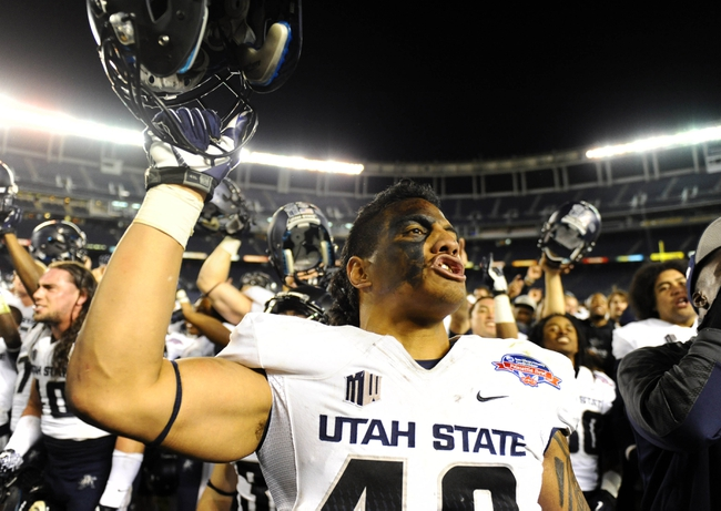 Dec 26, 2013; San Diego, CA, USA; Utah State Aggies defensive end Paul Piukala (48) celebrates after a win against the Northern Illinois Huskies during the 2013 Poinsettia Bowl at Qualcomm Stadium. The Aggies won 21-14. Mandatory Credit: Christopher Hanewinckel-USA TODAY Sports
