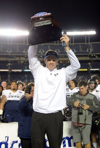 Dec 26, 2013; San Diego, CA, USA; Utah State Aggies coach Matt Wells hoists the championship trophy after the 2013 Poinsettia Bowl against the Northern Illinois Huskies at Qualcomm Stadium. Mandatory Credit: Kirby Lee-USA TODAY Sports