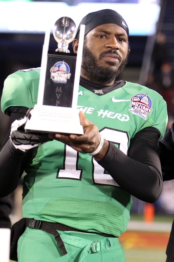Dec 27, 2013; Annapolis, MD, USA; Marshall Thundering Herd quarterback Rakeem Cato (12) accepts the MVP trophy after the game against the Maryland Terrapins during the 2013 Military Bowl at Navy-Marine Corps Memorial Stadium. Mandatory Credit: Mitch Stringer-USA TODAY Sports