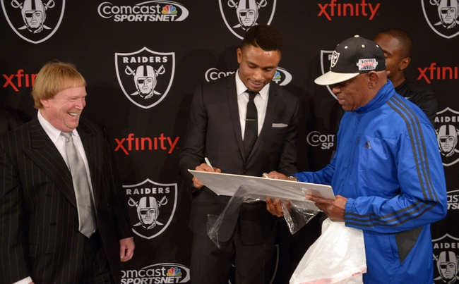 Dec 27, 2013; Alameda, CA, USA; Oakland Raiders former cornerback Nnamdi Asomugha (center) signs autograph for Cliff Branch as Raiders owner Mark Davis watches at press conference at Oakland Raiders Practice Facility. Mandatory Credit: Kirby Lee-USA TODAY Sports