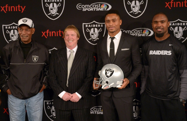 Dec 27, 2013; Alameda, CA, USA; Oakland Raiders former cornerback Nnamdi Asomugha poses at press conference to announce his retirement at Oakland Raiders Practice Facility. From left: Willie Brown and Mark Davis and Asomugha and Charles Woodson and Cliff Branch. Mandatory Credit: Kirby Lee-USA TODAY Sports