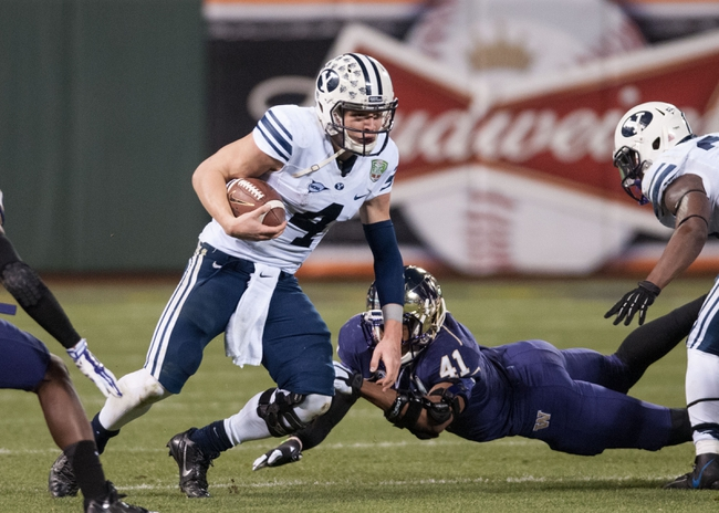 Dec 27, 2013; San Francisco, CA, USA; Brigham Young Cougars quarterback Taysom Hill (4) avoids a tackle by Washington Huskies linebacker Travis Feeney (41) during the second quarter at AT&T Park. Mandatory Credit: Ed Szczepanski-USA TODAY Sports