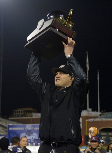 Dec 27, 2013; San Francisco, CA, USA; Washington Huskies interim coach Marques Tuiasosopo holds the championship trophy after the 2013 Fight Hunger Bowl against the BYU Cougars at AT&T Park. Washington defeated BYU 31-16. Mandatory Credit: Kirby Lee-USA TODAY Sports