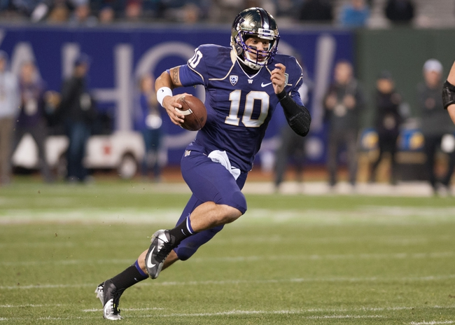 Dec 27, 2013; San Francisco, CA, USA; Washington Huskies quarterback Cyler Miles (10) rushes for a gain against the Brigham Young Cougars during the fourth quarter at AT&T Park. The Washington Huskies defeated the Brigham Young Cougars 31-16. Mandatory Credit: Ed Szczepanski-USA TODAY Sports