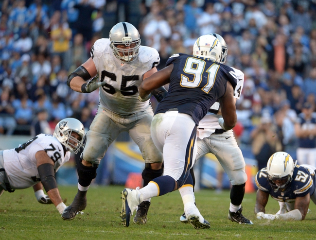 Dec 22, 2013; San Diego, CA, USA; Oakland Raiders guard Mike Brisiel (65) defends against San Diego Chargers defensive end Kendall Reyes (91) at Qualcomm Stadium. Mandatory Credit: Kirby Lee-USA TODAY Sports