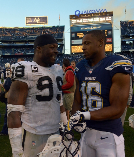 Dec 22, 2013; San Diego, CA, USA; Oakland Raiders defensive end Lamarr Houston (99) and San Diego Chargers receiver Seth Ajirotutu (16) after the game at Qualcomm Stadium. The Chargers won 26-13. Mandatory Credit: Kirby Lee-USA TODAY Sports