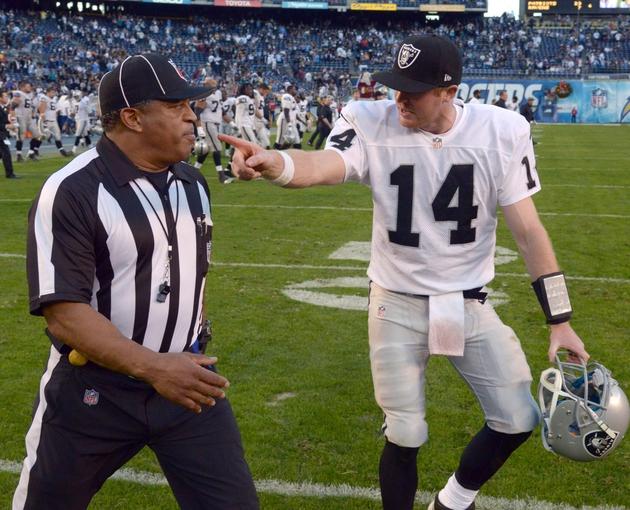 Dec 22, 2013; San Diego, CA, USA; Oakland Raiders quarterback Matt McGloin (14) confronts field judge Buddy Horton (82) after the game against the San Diego Chargers at Qualcomm Stadium. The Chargers won 26-13. Mandatory Credit: Kirby Lee-USA TODAY Sports