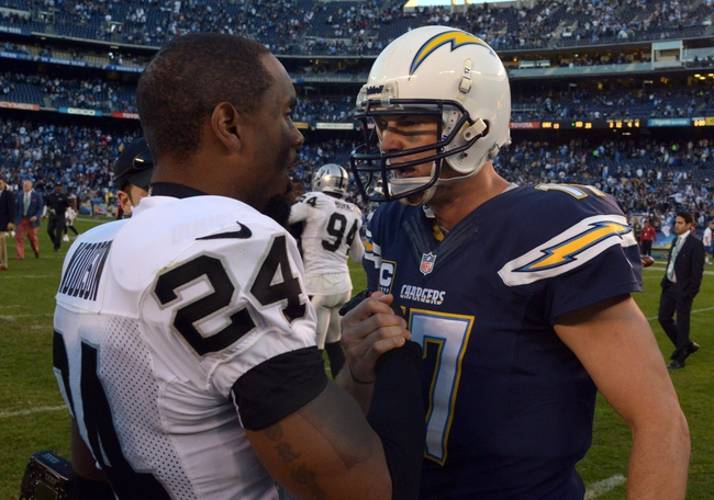 Dec 22, 2013; San Diego, CA, USA; Oakland Raiders safety Charles Woodson (24) and San Diego Chargers quarterback Philip Rivers (17) shake hands after the game at Qualcomm Stadium. The Chargers won 26-13.Mandatory Credit: Kirby Lee-USA TODAY Sports