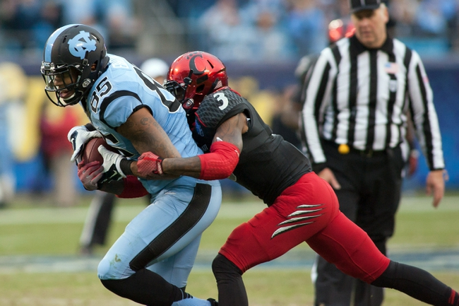 Dec 28, 2013; Charlotte, NC, USA; North Carolina Tar Heels tight end Eric Ebron (85) gets tackled by Cincinnati Bearcats defensive back Howard Wilder (3) during the second quarter at Bank of America Stadium. Mandatory Credit: Jeremy Brevard-USA TODAY Sports