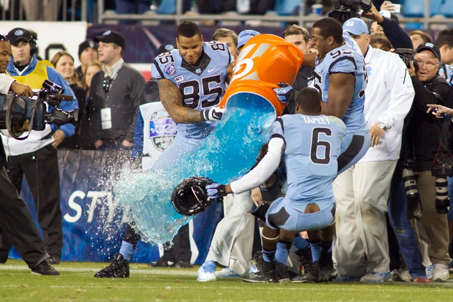 Dec 28, 2013; Charlotte, NC, USA; North Carolina Tar Heels tight end Eric Ebron (85) and defensive end Kareem Martin (95) dump gatorade on head coach Larry Fedora in the Belk Bowl at Bank of America Stadium. Carolina defeated Cincinnati 39-17. Mandatory Credit: Jeremy Brevard-USA TODAY Sports