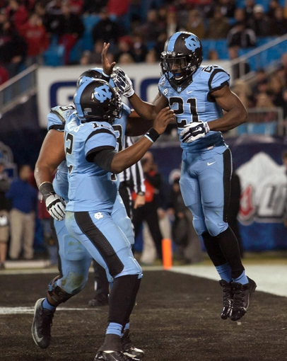 Dec 28, 2013; Charlotte, NC, USA; North Carolina Tar Heels running back Romar Morris (21) celebrates after scoring a touchdown during the third quarter against the Cincinnati Bearcats in the Belk Bowl at Bank of America Stadium. Carolina defeated Cincinnati 39-17. Mandatory Credit: Jeremy Brevard-USA TODAY Sports