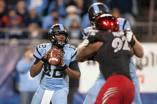 Dec 28, 2013; Charlotte, NC, USA; North Carolina Tar Heels quarterback Marquise Williams (12) looks to pass the ball during the third quarter against the Cincinnati Bearcats in the Belk Bowl at Bank of America Stadium. Carolina defeated Cincinnati 39-17. Mandatory Credit: Jeremy Brevard-USA TODAY Sports