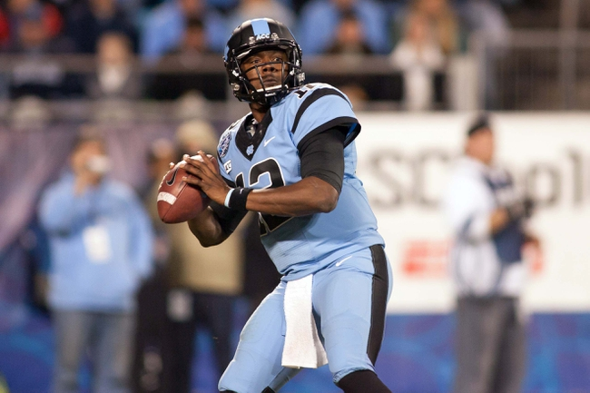 Dec 28, 2013; Charlotte, NC, USA; North Carolina Tar Heels quarterback Marquise Williams (12) passes the ball during the third quarter against the Cincinnati Bearcats in the Belk Bowl at Bank of America Stadium. Carolina defeated Cincinnati 39-17. Mandatory Credit: Jeremy Brevard-USA TODAY Sports
