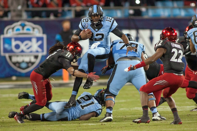 Dec 28, 2013; Charlotte, NC, USA; North Carolina Tar Heels quarterback Marquise Williams (12) jumps over a teammate during the third quarter against the Cincinnati Bearcats in the Belk Bowl at Bank of America Stadium. Carolina defeated Cincinnati 39-17. Mandatory Credit: Jeremy Brevard-USA TODAY Sports