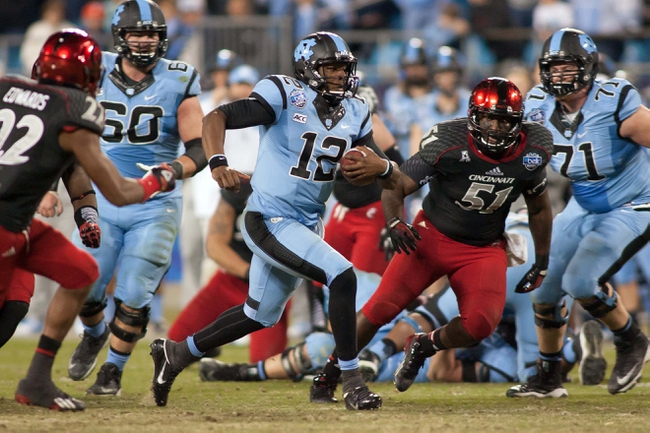 Dec 28, 2013; Charlotte, NC, USA; North Carolina Tar Heels quarterback Marquise Williams (12) runs the ball during the third quarter against the Cincinnati Bearcats in the Belk Bowl at Bank of America Stadium. Carolina defeated Cincinnati 39-17. Mandatory Credit: Jeremy Brevard-USA TODAY Sports