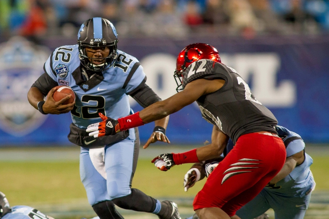 Dec 28, 2013; Charlotte, NC, USA; North Carolina Tar Heels quarterback Marquise Williams (12) runs the ball during the fourth quarter against the Cincinnati Bearcats in the Belk Bowl at Bank of America Stadium. Carolina defeated Cincinnati 39-17. Mandatory Credit: Jeremy Brevard-USA TODAY Sports